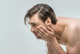Side of a man washing his face