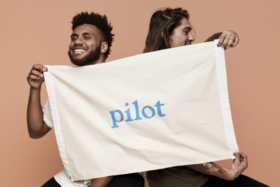 Two man holding a cloth with Pilot logo in center