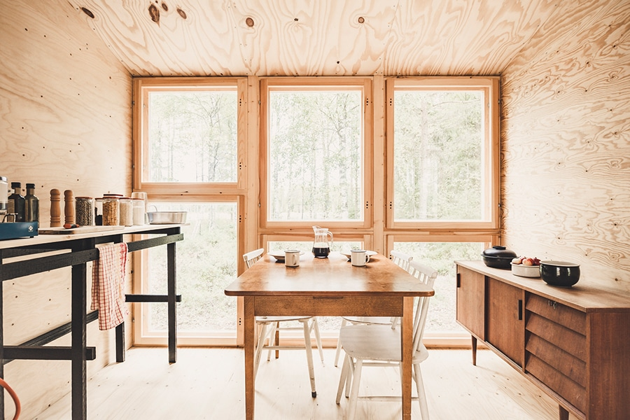 wood cabin kitchen with dining table in the centre