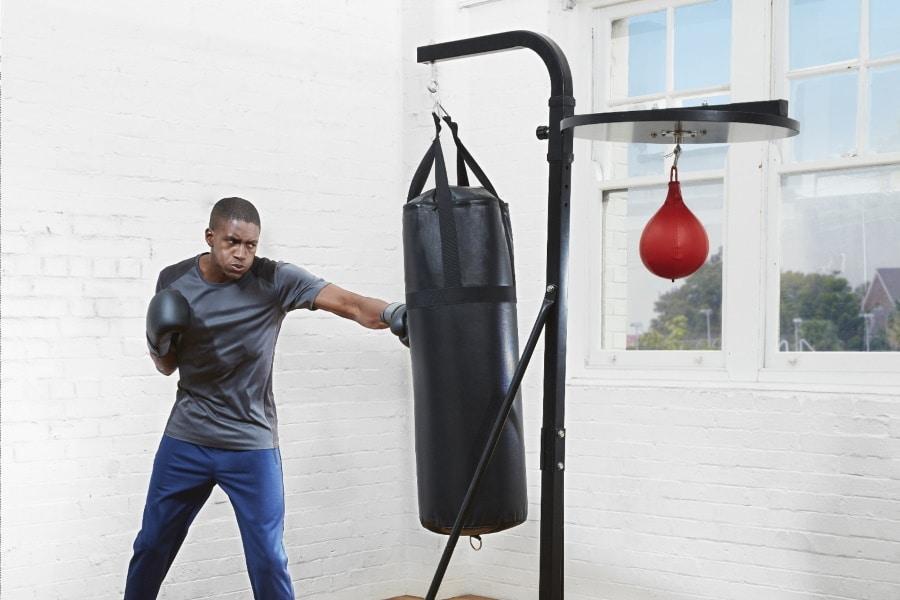 A man punching punching bag hanging by Aldi Boxing Toer