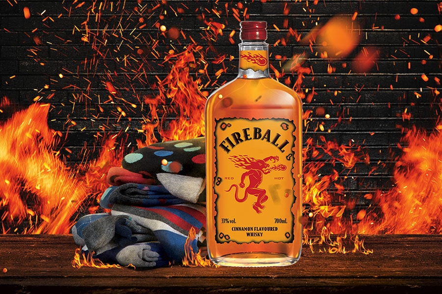 Bottle of Fireball with fire graphics in background