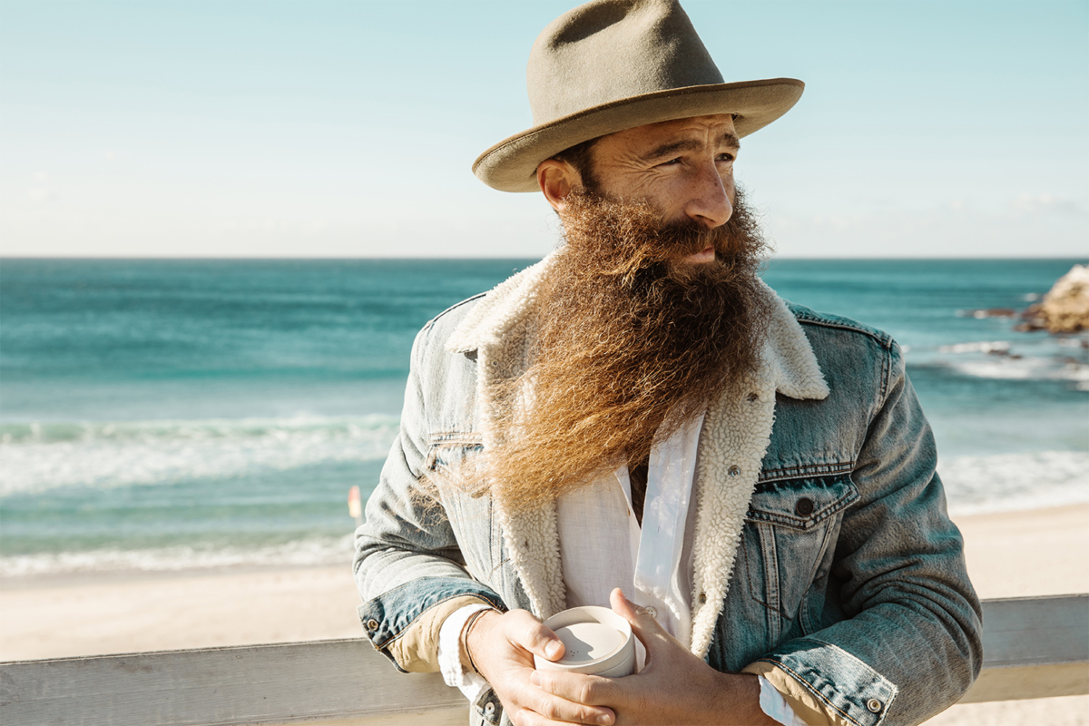 Man with a long beard with beach in background