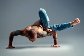 A man balancing his body on his hands in a Yoga position