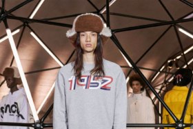 Model wearing a bomber hat and gray t-shirt with 1952 graphic on chest