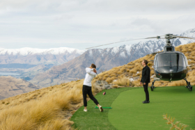 Jimmy playing golf on a mountain next to a helicopter hitting the ball down the mountain