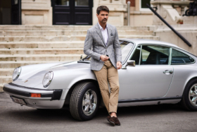 Man in a gray coat over white shirt and khakis standing with his back leaning on front fender of a Porsche 911