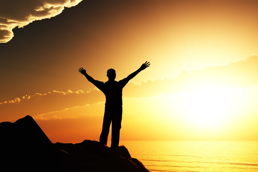 Silhouette of a man on a hill with his arms raised in air in front of sun