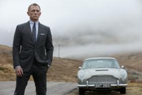 Daniel Craig withAston Martin DB5 in background next to him