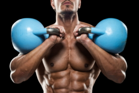 A man holding two kettlebells touching his shoulders