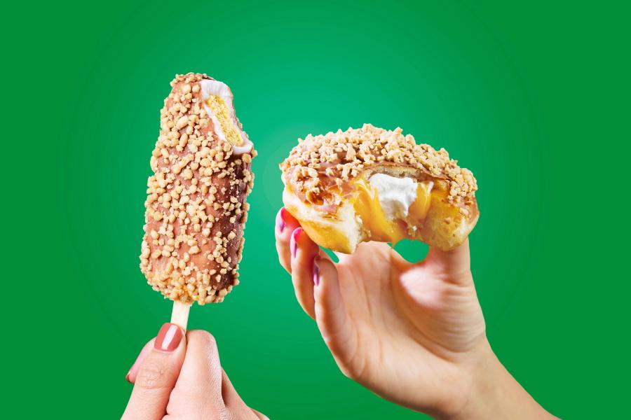 Hands holdingGolden Gaytime Krispy Kreme andhalf-eaten Krispy Cream Golden Gaytime Donut