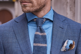 Model in a gray suit over a blue shirt