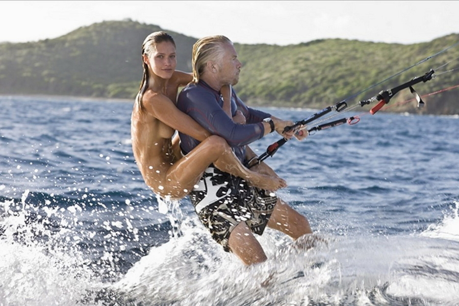A naked woman riding back of Richard Branson on a water glider
