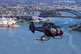 A black helicopter flying over Sydney with Harbour Bridge in background