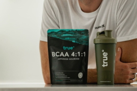 true BCAA 4:1:1 bag and true shaker on a table with a man in background