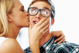 A woman kissing cheek of a man holding his mouth with one hands