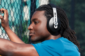 Profile of a man wearing headphones sitting near a wire fence