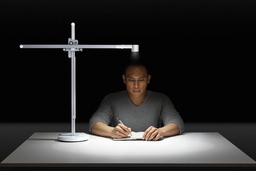 Man writing next to Dyson Lightcycle Task Desk Light