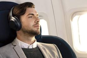 A man wearing headphones sitting on a flight seat
