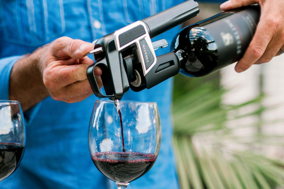 A man pouring wine from Coravin Model Two Premium Wine Preservation System in a wine glass