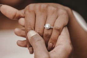 A hand holding someone's hand wearing an engagement ring