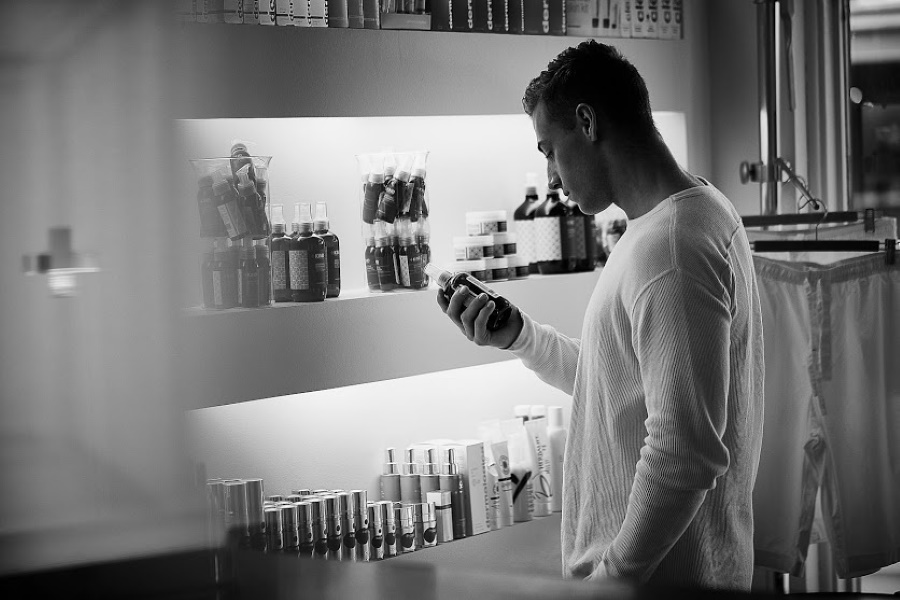 A man looking at a bottle in his hand at a shop