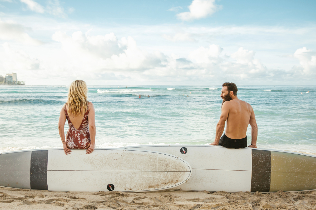Backs of Jimmy and Emma sitting on edges of their surfboard standing on sides in beach sand