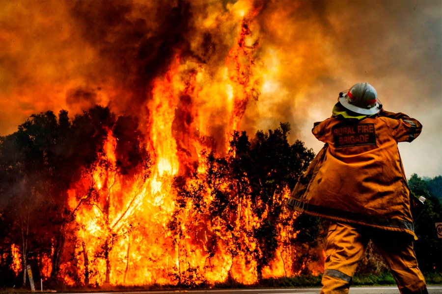 A Rural Fire Brigade Fireman in front of a large bushfire
