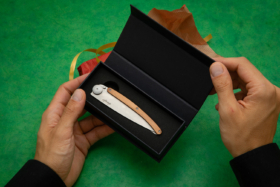 Pair of hands holding a Deejo knife in its box