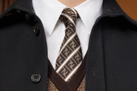 Closeup of a the chest of a man in suit with a Fendi tie