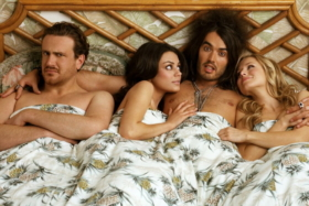 A man in bed with two women on his sides and a man on left with an angry face