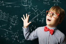 A kid with glasses in front of a greenboard with diagram