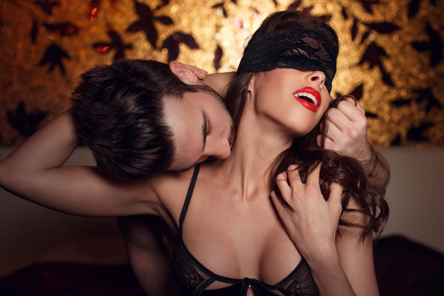 A man kissing neck of a blindfolded woman from behind