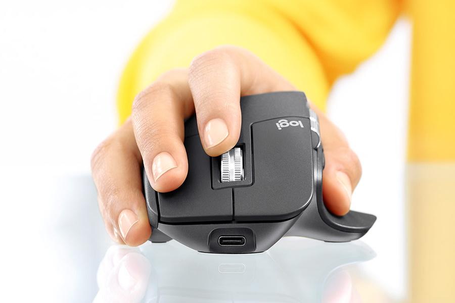 A hand holdingLogitech MX Master 3 Mouse