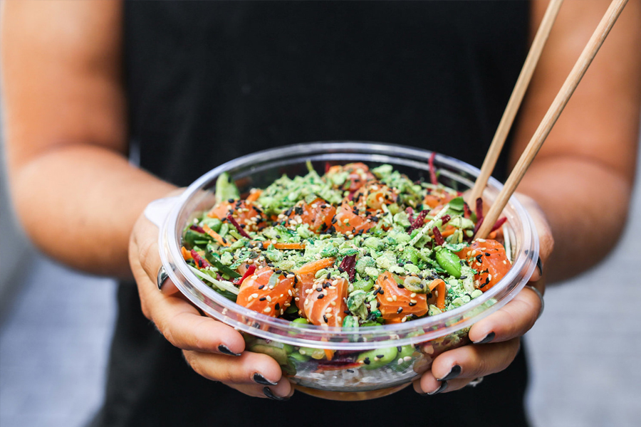 Pair of hands holding a poke bowl