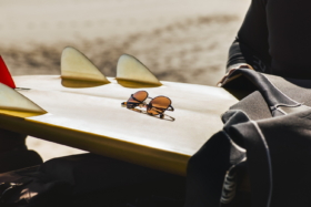 Sunglasses on a turned over surfboard