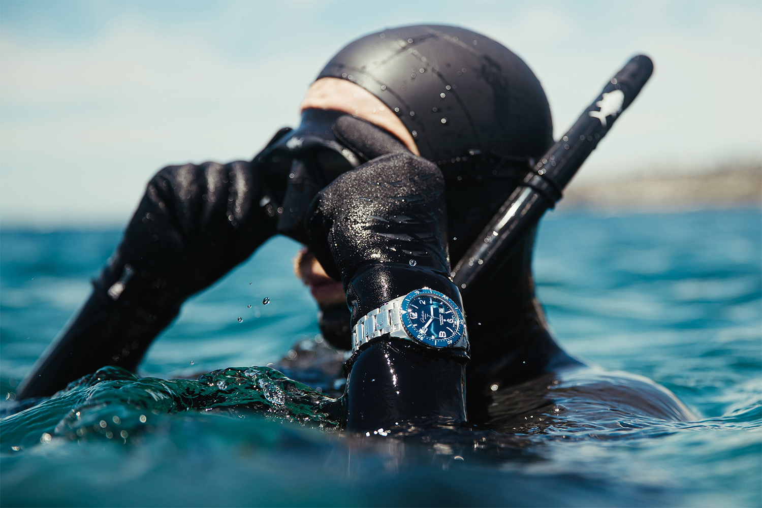 A diver in black wetsuit on surface wearing Glashütte Original watch