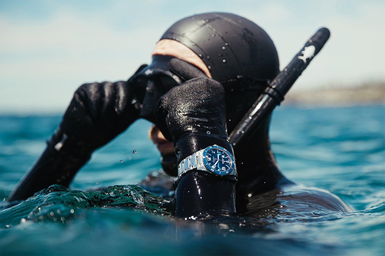 A diver in black wetsuit on surface wearingGlashütte Original watch