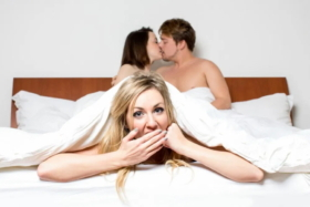 A woman under blanket with her hand on her mouth as a couple kiss in background at the head of bed