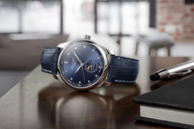A blue dial Longines watch on its side