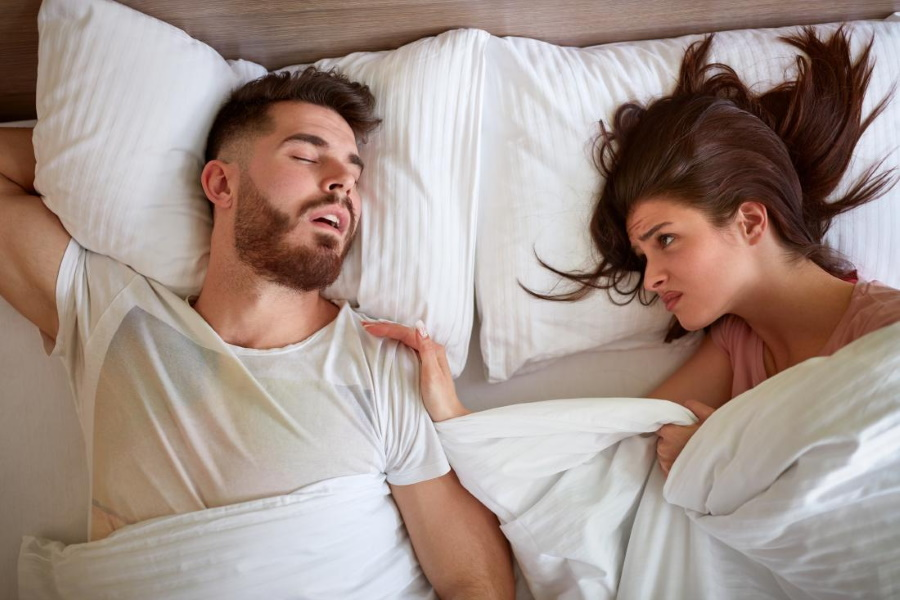 A man sleeping in bed next to an angry wife
