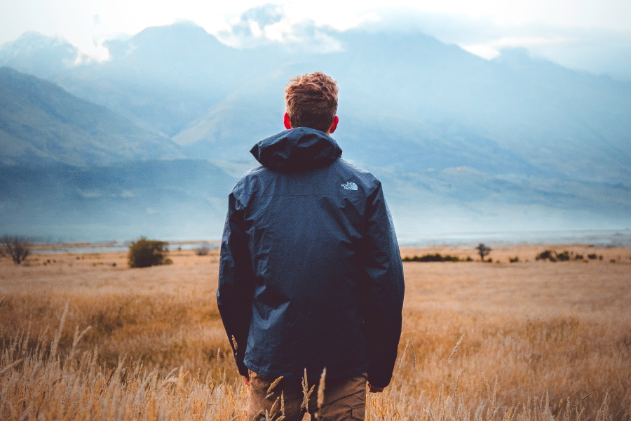 Back of a man looking towards mountains far away