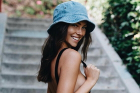 Portrait of a girl wearing a denim bucket hat pulling strap of her top with a thumb