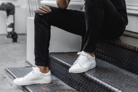 Legs of a model in black jeans and white sneaker