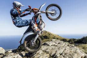 A dirt biker doing a wheelie on a rock