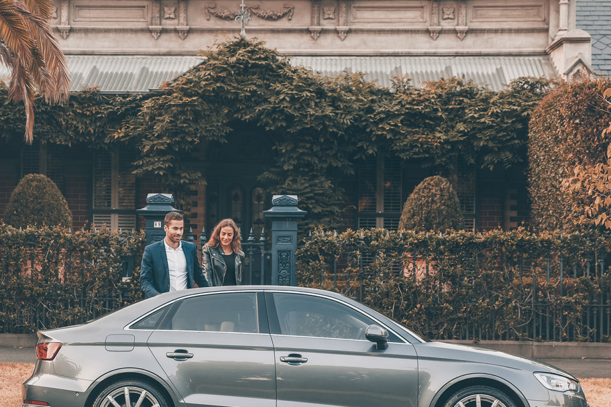 A man and a woman on the other side of a parked car