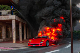 A red Ferrari F40 on fire on a road