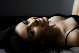 A woman in black lingerie lying on bed looking back