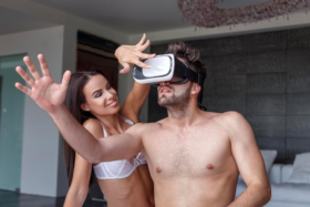 A woman holding a finger on a man's VR headset who is reaching out for nothing