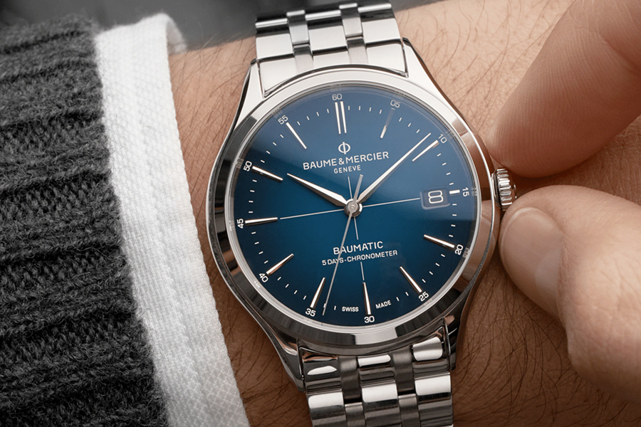 A Clifton Baumatic 10468 watch on a wrist being wound by a hand