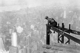 A man working sitting on a steel bar at top of Chrysler Building during construction